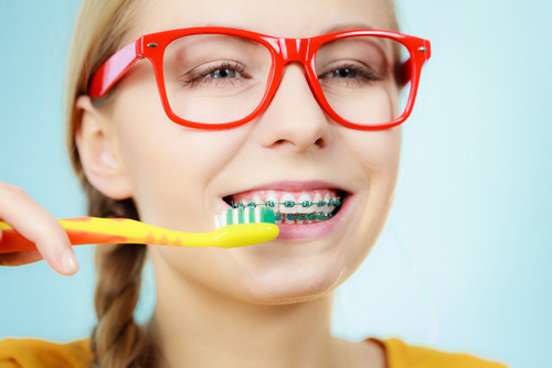 Teen girl being shows how to brush her braces by her Orthodontist at Dr. Tim Dumore & Team.